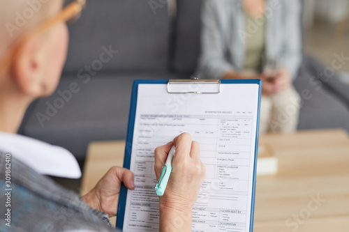 Cuadros en Lienzo  High angle closeup of female psychologist filling in medical form while talking