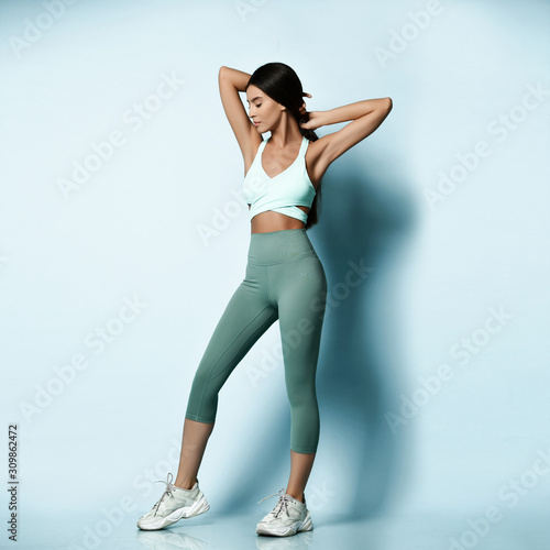 Beautiful sportswoman in sportswear working out doing stretching sports exercise Wallpaper Mural