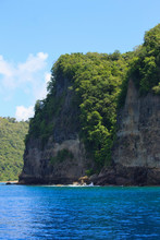 Enchanting View Of A Cliff Face Partially Covered With Green Vegetation Above The Most Inviting Blue Sea Water On A Bright Day In The Summer