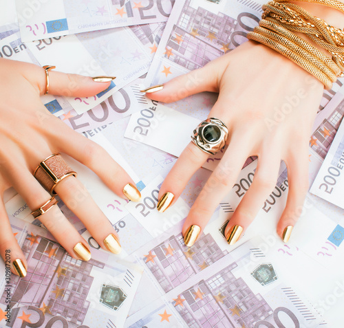 Fototapeta hands of rich woman with golden manicure and many jewelry rings on cash euros obraz