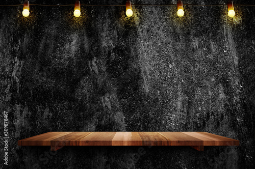 Obraz Empty brown plank wood shelf at black grung concerte wall background with light bulbs string,Mockup for display or montage of product or design - fototapety do salonu