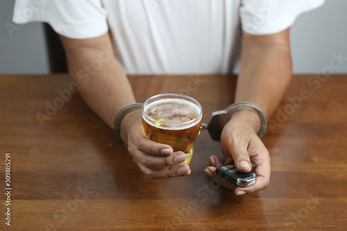 Obraz na plátně  Do not drink and drive concept, Man hand holding glasses of beer with car keys a