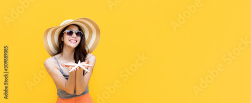 Cuadros en Lienzo  Asian woman in summer casual clothes smiling and holding starfish in hands