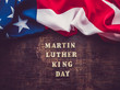 Wooden unpainted letters of the alphabet on a dark background. Martin Luther King Jr. Day. Top view, close-up. National holiday concept