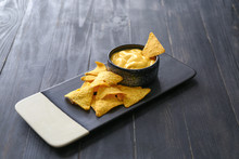 Board With Tasty Nachos And Sauce On Dark Table