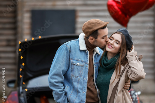 Photo Happy young couple near car outdoors. Valentine's Day celebration