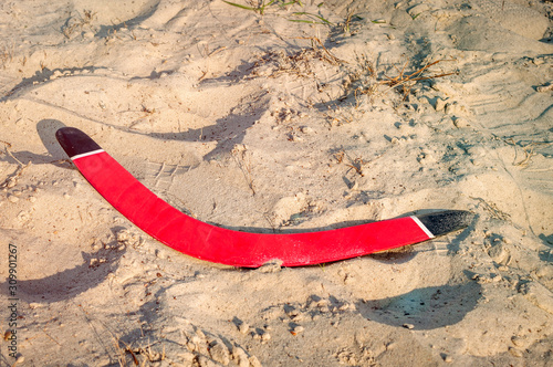 Photo Red wooden boomerang lies in the sand
