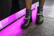 canvas print picture - Fashionable black shoes on a girl in a shopping center near purple lights, bright showy photos