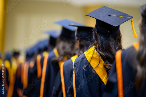 The back of the graduates are walking to attend the graduation ceremony at the u Wallpaper Mural