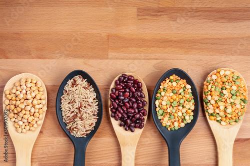 Bean grains in tablespoons on a wooden background Tapéta, Fotótapéta
