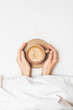 canvas print picture - Female hands are holding a cup of morning coffee on the background of a white bedsheet under the covers in bed. Concept wake. Top view. Flat lay