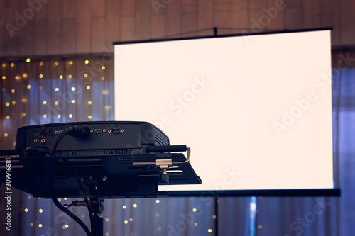 Photo A view to the projection screen equipment at the decorated window curtain background of a banquet hall