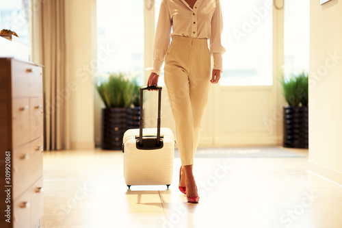 Fotografia Businesswoman with luggage in modern hotel lobby