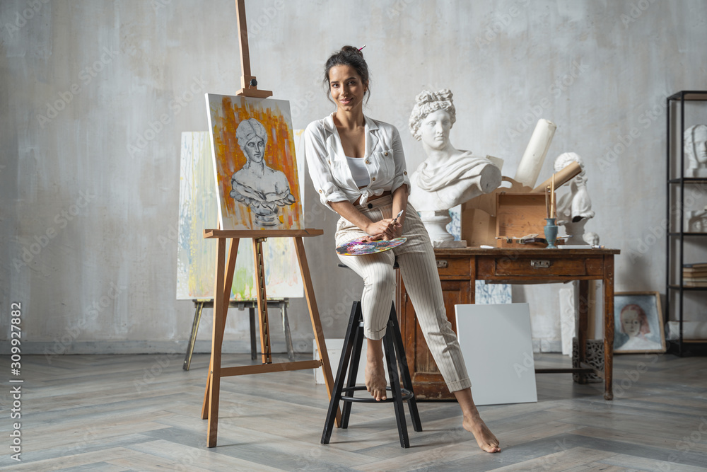 Fototapeta Satisfied female artist posing near new picture next to easel