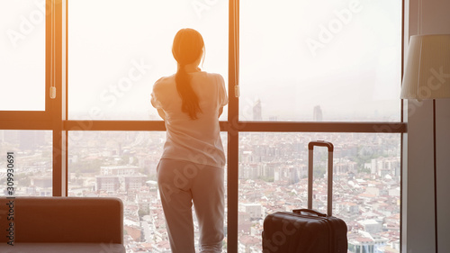 Fototapety, obrazy: Young brunette woman traveler with suitcase in hotel room with panoramic city view. She is standing near the window and looking at city, sunlight