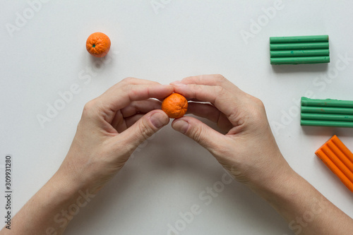 Fotografía  Woman hands holding small orange fruit made from polymer clay on white backgroun