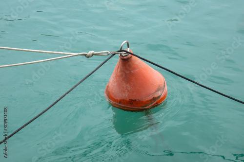 Fotografija galleggiante legato nello specchio d'acqua del mare