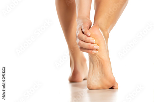 Fotografía woman touching her painful heel on white background