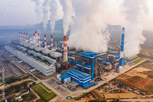 Fototapeta Aerial view of Mae Moh Coal Power Plant with smoke and toxic air from chimney. Factory industry. Electricity tower in energy or pollution environment concept. Lampang City, Thailand obraz