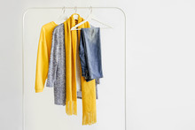 Female Clothes In Yellow And Blue Color On Hanger On White Background.  Jumper, Shirt And Scarf. Spring/autumn Outfit. Minimal Concept.