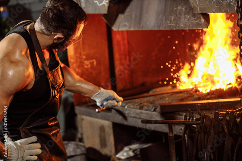 Photo caucasian young strong blacksmith working with open fire in furnace