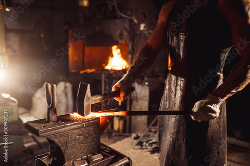 young bearded man in leather uniform heats the metal on fire isolated in worksho Fototapete