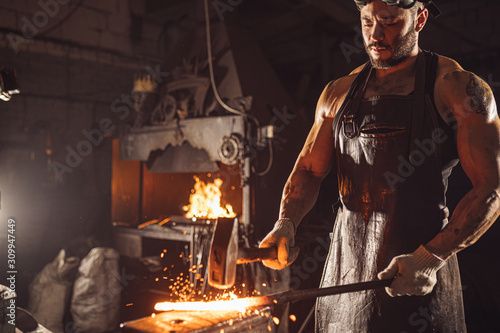 Fototapeta caucasian young man forger having muscular body beat iron with hammer isolated in dark whorkshop