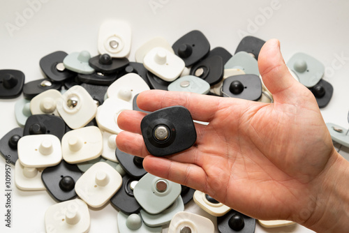 many multi-colored anti-theft sensor on a man's male hand on a light background Wallpaper Mural