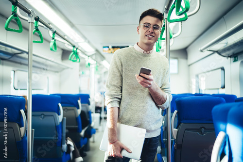 Fototapety, obrazy: Cheerful man with smartphone standing in train