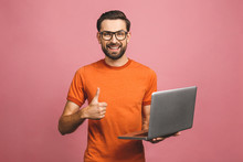 Confident Business Expert. Confident Young Handsome Man In Casual Holding Laptop And Smiling While Standing Against Pink Background. Thumbs Up.