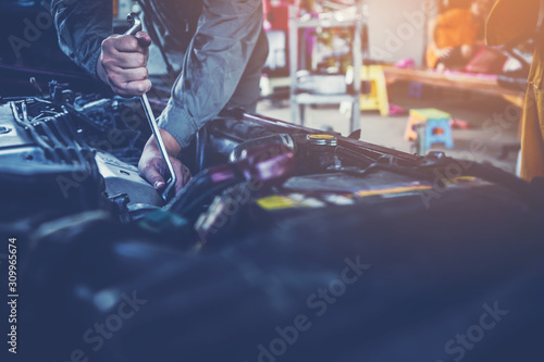 Fotografía  technician working on checking and service car in  workshop garage; technician r