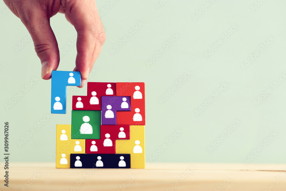 Fototapeta Business concept image of tangram puzzle blocks with people icons over wooden table, human resources and management concept