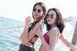 Two beautiful asian women wearing bikini and standing beside the sea