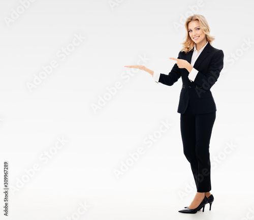 Obraz Full body portrait of happy smiling young businesswoman in black confident suit, showing something or blank copy space for some slogan or text, over grey background - fototapety do salonu