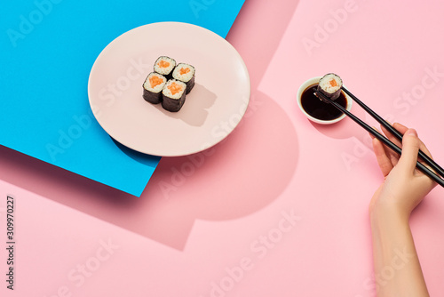 Fototapeta cropped view of woman eating fresh maki with salmon near soy sauce on blue, pink background obraz