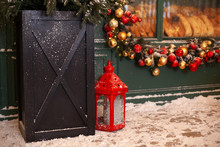 Christmas Lantern In Snow With A Christmas Tree And Garland With Toys In Evening Scene. Christmas Lantern Stands In Backyard On Terrace. Christmas Red Lantern On Street. Vintage Xmas Decoration.