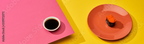 Fototapeta fresh maki with red caviar on plate near soy sauce on pink, yellow surface, panoramic shot obraz