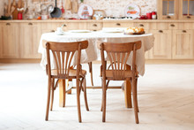 Stylish Kitchen Interior With Wooden Table And Chairs. Wooden Dining Table For 4 People. Stylish Kitchen Interior. Rustic Kitchen Interior. Scandinavian Dining Room In Cottage Style. Eco Furniture