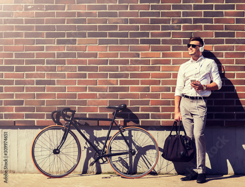 people, technology and lifestyle - happy young man with headphones, smartphone and bicycle listening to music in city - 309974651