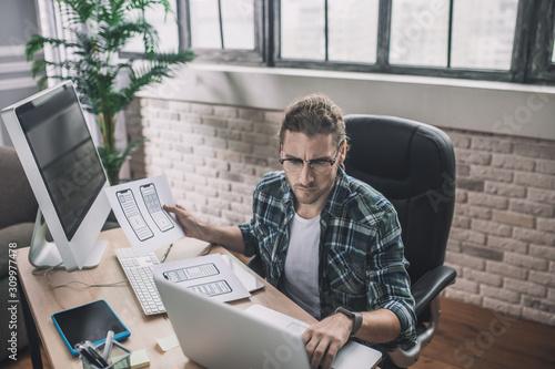 Fototapeta Young man in eyeglasses sitting at the desk obraz na płótnie