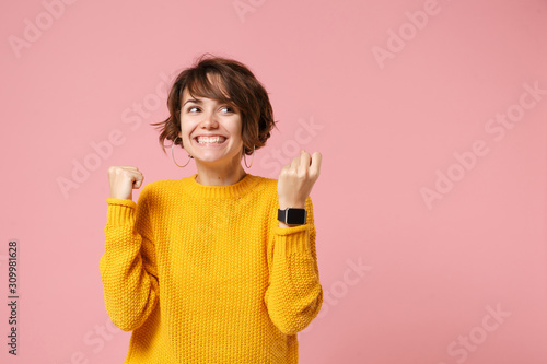 Fotografía Joyful young brunette woman girl in yellow sweater posing isolated on pink background studio portrait