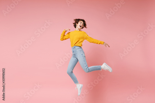 Funny young brunette woman girl in yellow sweater posing isolated on pastel pink background in studio Canvas Print