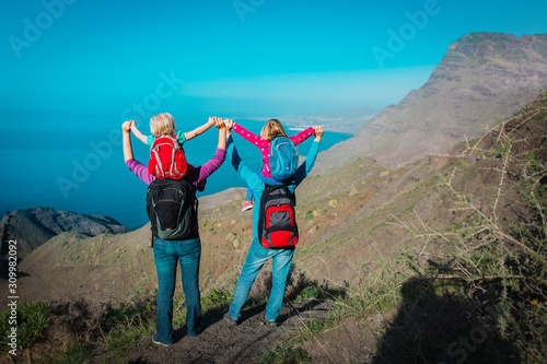 Fotografia  happy mom, dad with kids travel in mountains near sea, family in Canary islands,