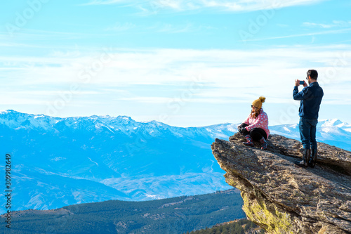 Obraz Almeria, Spain, December 14, 2019: Couple taking pictures over a rock against idyllic view of mountain range high at Calar alto observatory, in Andalusia, Spain. - fototapety do salonu