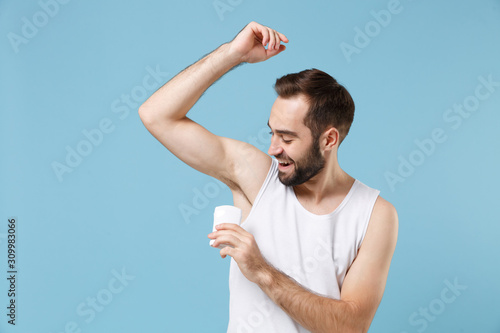 Bearded young man 20s years old in white shirt hold using antiperspirant isolated on blue pastel wall background, studio portrait Canvas Print