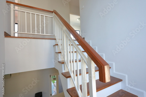 Foto brown wooden stair with white steel balustrade and hardwood handrail banister in