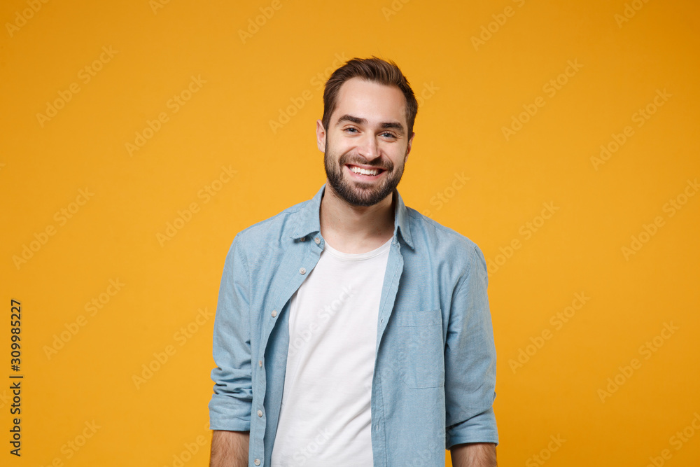 Fototapeta Smiling handsome young bearded man in casual blue shirt posing isolated on yellow orange wall background studio portrait. People sincere emotions lifestyle concept. Mock up copy space. Looking camera.