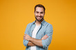 Smiling young bearded man in casual blue shirt posing isolated on yellow orange wall background, studio portrait. People sincere emotions lifestyle concept. Mock up copy space. Holding hands crossed.