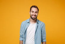 Smiling Handsome Young Bearded Man In Casual Blue Shirt Posing Isolated On Yellow Orange Wall Background Studio Portrait. People Sincere Emotions Lifestyle Concept. Mock Up Copy Space. Looking Camera.