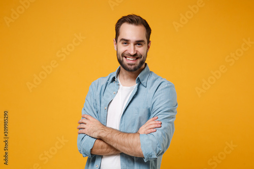Fotografía Smiling young bearded man in casual blue shirt posing isolated on yellow orange wall background, studio portrait